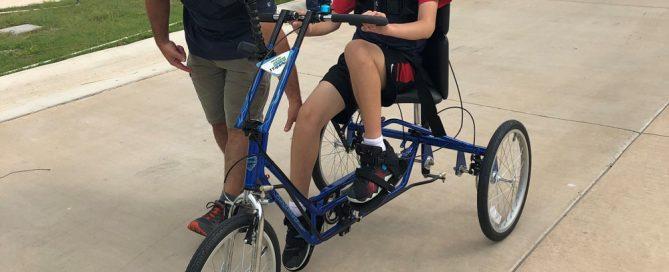 Jordan's dad, Tony, helps Jordan get onto his new Freedom Concepts Adaptive Bicycle