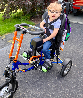 Karter Goodchild Poses For a Picture on His Adaptive Bicycle